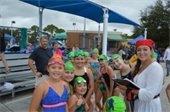 A swim coach in costume with swim team members