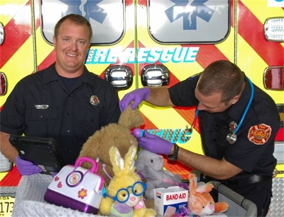 "An EMT and a Paramedic ""examining"" some stuffed bunnies."